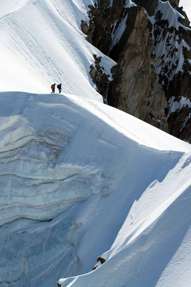 An extreme wide shot of two mountaineers climbing a snowy mountain
